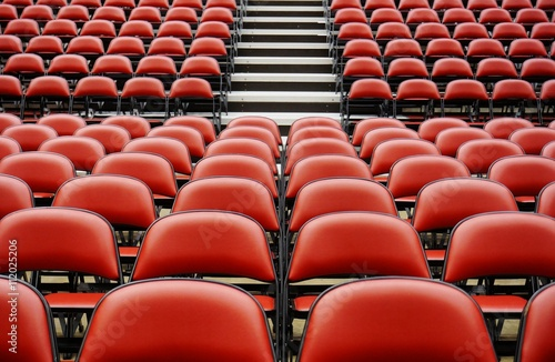 Fotografie, Obraz  Folded red seats at a multipurpose arena and sports stadium