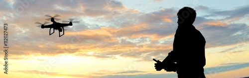 Obraz man operating of flying drone quadrocopter at sunset - fototapety do salonu