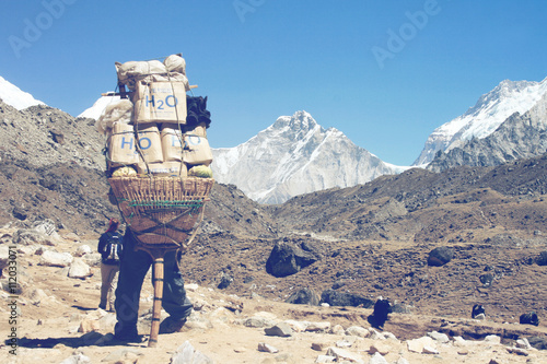 Wall Murals Nepal Sherpa carrying a large load on his back