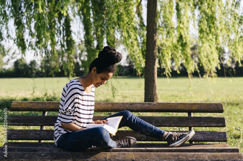 Young woman sitting on park bench reading a book