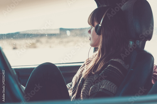 Young woman travelling in car listening music