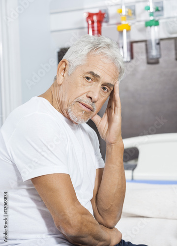 b3107d55fa2 Sad Male Patient Sitting On Bed At Rehab Center - Buy this stock ...