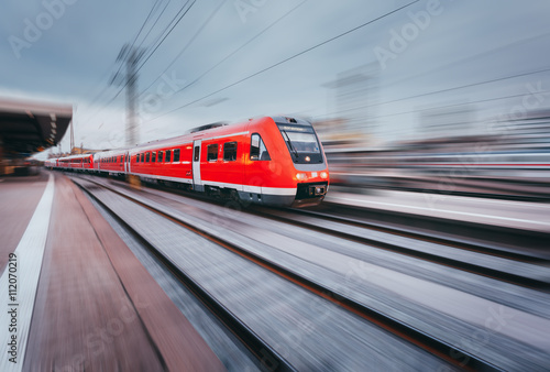 Railway station with modern high speed red passenger train at sunset in Nuremberg, Germany Canvas Print