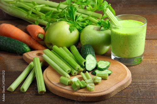 Fresh sliced green celery on wooden cutting Board with cucumber near juice in a glass and a pile of vegetables on brown wooden background