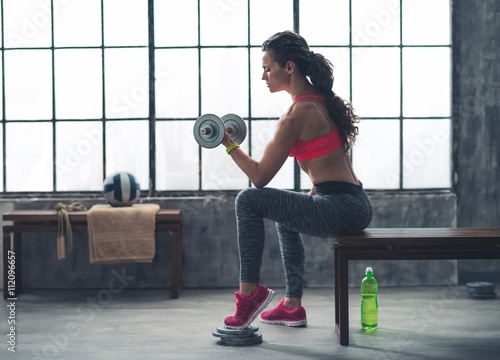 plakat Fitness woman lifting dumbbell in urban loft gym