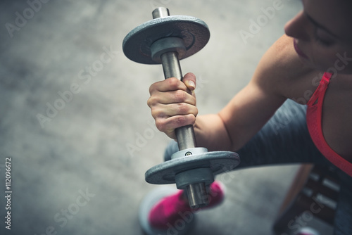 Fototapeta Closeup on fitness woman workout with dumbbell in urban loft gym obraz