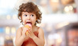 canvas print picture - Kid eating ice cream in cafe. Funy curly child with icecream outdoor.