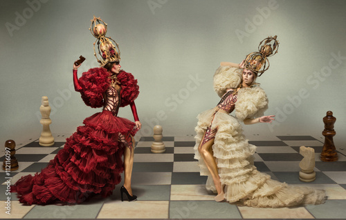 Fotografia  Battle of chess queens on chess board with chess figures on background
