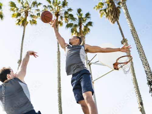 Two young men playing basketball on an outdoor court Poster