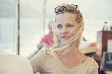 Piękna kobieta z rozwianymi wiatrem blond włosami podróżująca statkiem