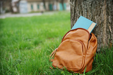 Leather Backpack With Book On Green Grass Outdoors