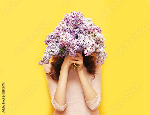 Fotomural  Woman hiding head in bouquet lilac flowers over yellow backgroun