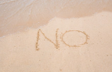 NO Sign Written In Sand On Beach Texture Sunny Background. Closeup