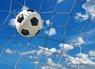 Obraz na SzkleFußball fliegt ins Tor vor blauem Wolkenhimmel