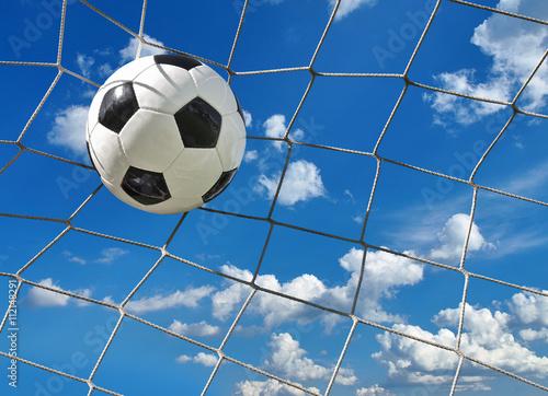 Fußball fliegt ins Tor vor blauem Wolkenhimmel - 112148291
