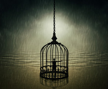 Man Standing Closed In A Bird Cage With Wide Opened Hands In Front Of The Ocean Horizon In A Rainy Day. Life Limitation, Trapped In A Prison Concept