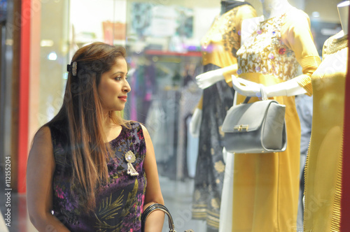 2e1787c274 Woman eyeing Indian suits in clothing shop. A beautiful young Indian woman  looking at the