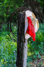 Cowboy Hat With Red Bandana Hanging On Fence Post On Country Road