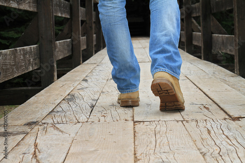 Fototapeta Man wearing lumberjack boots walking on old wooden bridge close up. Hunter fisherman Adventure man style. Travel, Wanderlust concept. obraz na płótnie