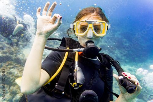 Fotografie, Obraz  Frau beim Tauchen im Urlaub Korallen Riff gibt das OK Zeichen