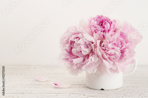 Foto  beautiful pink peonies in an enamel mug on a wooden desk, copyspace