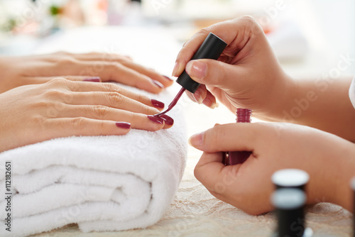 Photo sur Toile Manicure Side view of manicurist applying marsala nail polish