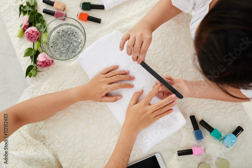 Photo  Manicurist filing nails of female client, view from above