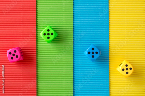 Four dices on colored corrugated paper Obraz na płótnie