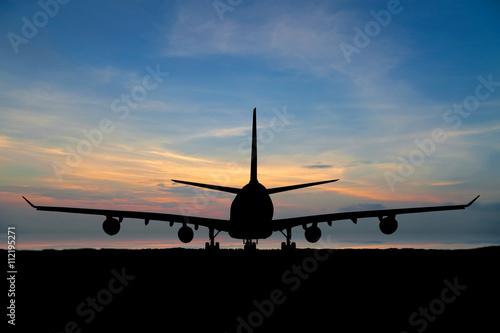 Tuinposter Vliegtuig Silhouette of passenger aircraft, airline on beautiful sunset