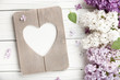 Lilac flowers background with blank heart shaped photo frame