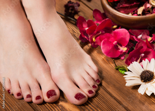 Tuinposter Pedicure Beautiful classic red pedicure on female hand. Close-up.
