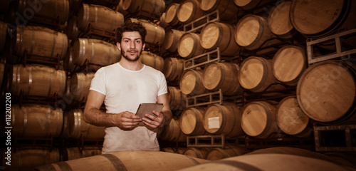 Fotografía  Winemaker counting the barrels with a tablet in large storage