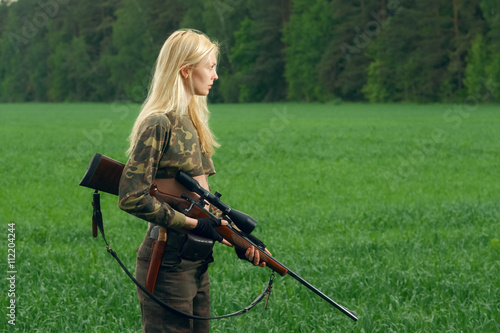 Pretty hunter girl with hunting rifle in the outer wood. Carbine