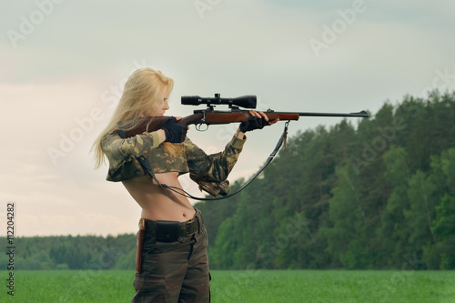 Poster Chasse Pretty hunter girl aiming with hunting rifle in the outer wood.