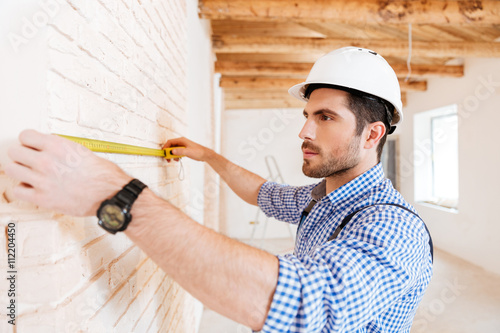 Close-up portrait of builder measuring wall using yellow type