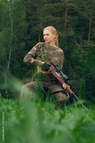 Poster Jacht Attractive hunter girl with hunting carbine looking out the trop