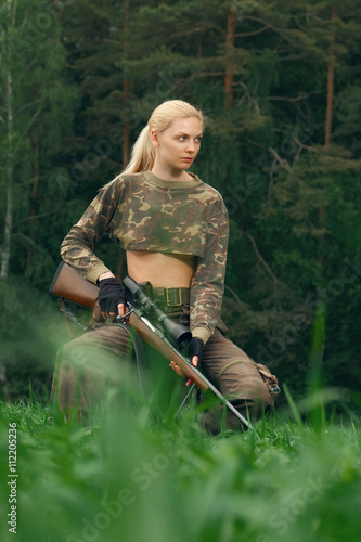 Fotobehang Jacht Attractive hunter girl with hunting carbine looking out the trop