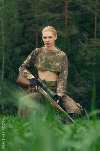 Foto op Canvas Jacht Attractive hunter girl with hunting carbine looking out the trop