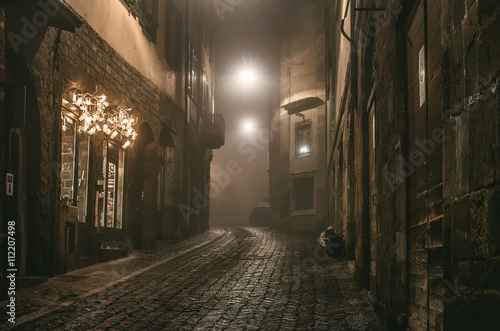 Fototapeta Old European narrow empty street of medieval town on a foggy evening