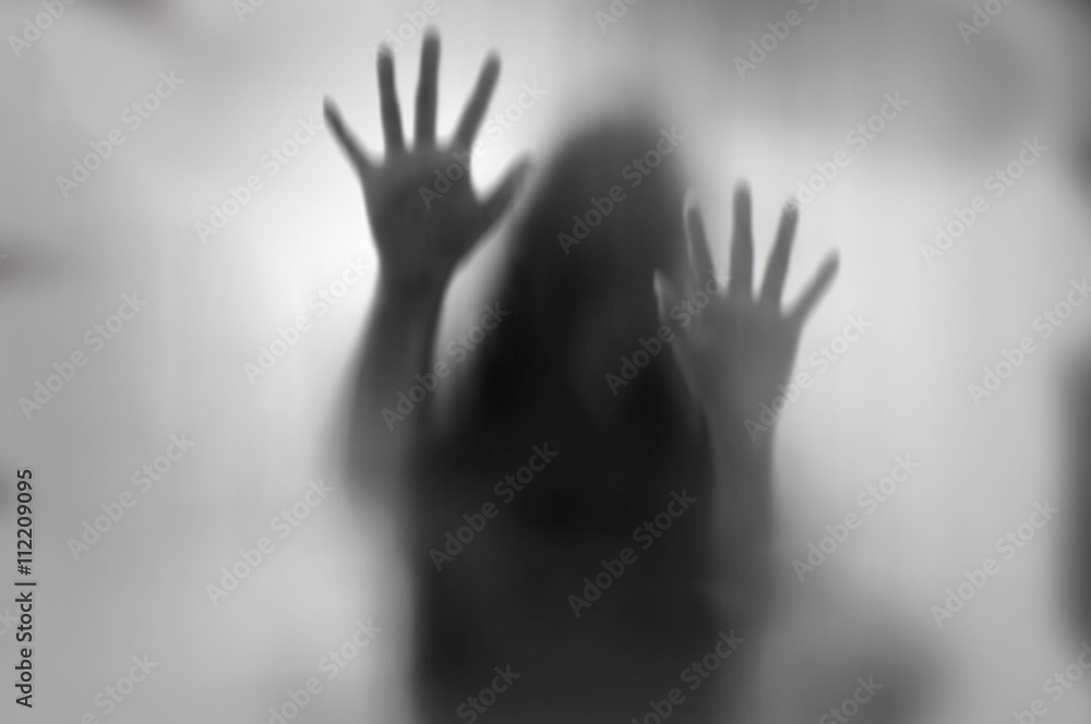 Fototapeta Horror woman behind the matte glass in black and white. Blurry hand and body figure abstraction