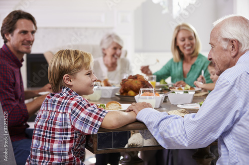 Fotografía  Extended Family Group Sit Around Table Eating Meal At Home