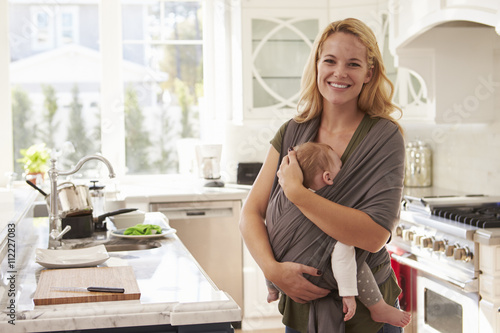 Fotografia  Portrait Of Busy Mother With Baby In Sling At Home