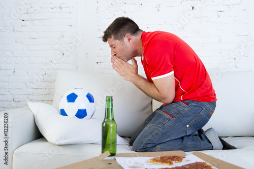 young man watching football game on television nervous and