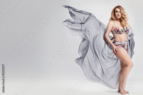 Plus size model wearing lingerie and piece of waving fabric Tablou Canvas