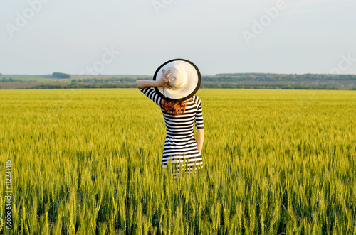 A slender girl in a striped dress and hat, seen from behind. Wallpaper Mural