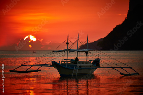 Canvas Prints Red Traditional filippino boat at El Nido bay in sunset lights.