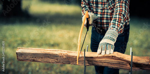 Senior man sawing a log handsaw closeup Canvas-taulu