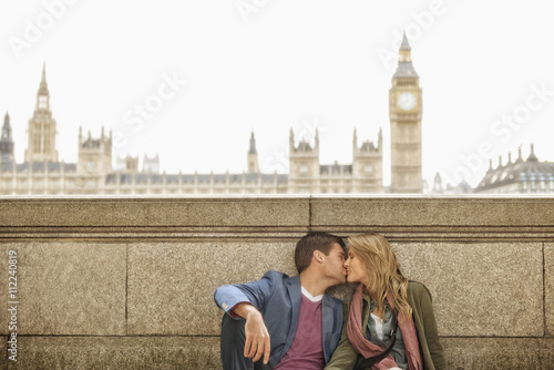 Caucasian couple kissing at clock tower, London, Middlesex, United Kingdom Poster