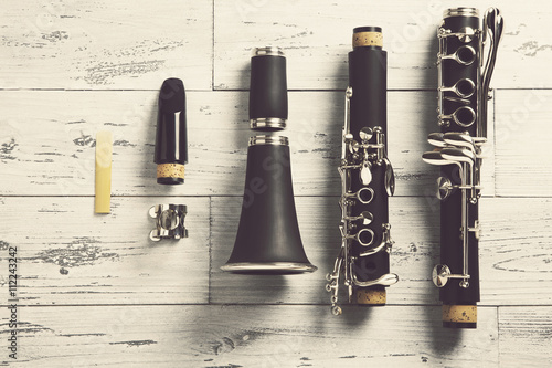Photo disassembled clarinet / overhead of a disassembled clarinet on wood top