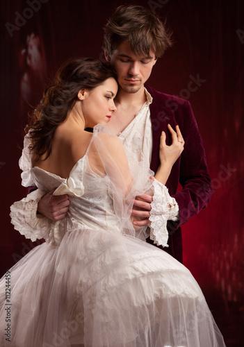 Foto  Hübsche junge Dame in der alten Zeit und Mann im roten mittelalterlichen Kleid